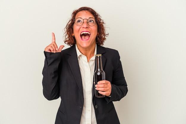 Mulher de negócios latinos de meia-idade segurando uma cerveja isolada no fundo branco, apontando para cima com a boca aberta.