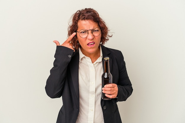 Mulher de negócios latinos de meia-idade segurando uma cerveja isolada no fundo branco, mostrando um gesto de decepção com o dedo indicador.