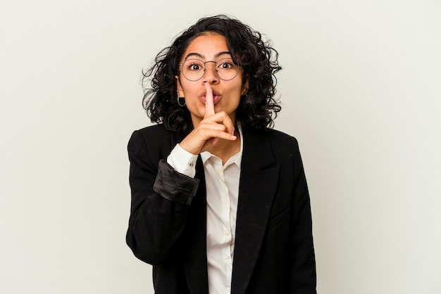 Mulher de negócios latinos jovem isolada no fundo branco, mantendo um segredo ou pedindo silêncio.