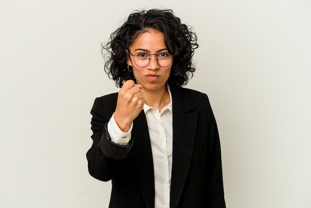 Mulher de negócios latinos jovem isolada no fundo branco, mostrando o punho para a câmera, expressão facial agressiva.