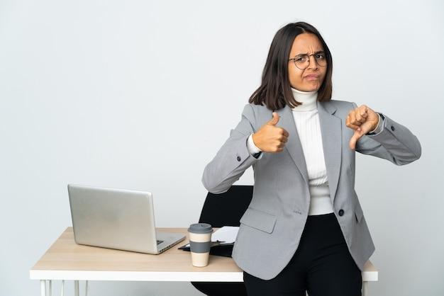 Mulher de negócios latinos jovem, trabalhando em um escritório isolado no branco, fazendo sinais de bom-ruim. indeciso entre sim ou não