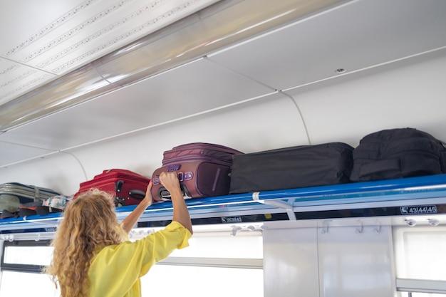 Mulher de negócios levando a bolsa do compartimento de bagagem no trem férias férias turismo viagens tr ...