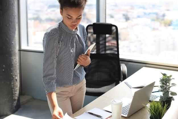 Mulher de negócios linda afro-americana em smart casual wear, trabalhando no laptop no escritório.