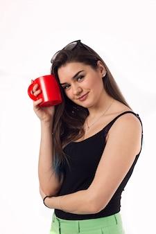 Mulher de negócios linda bebendo café chá de um copo vermelho