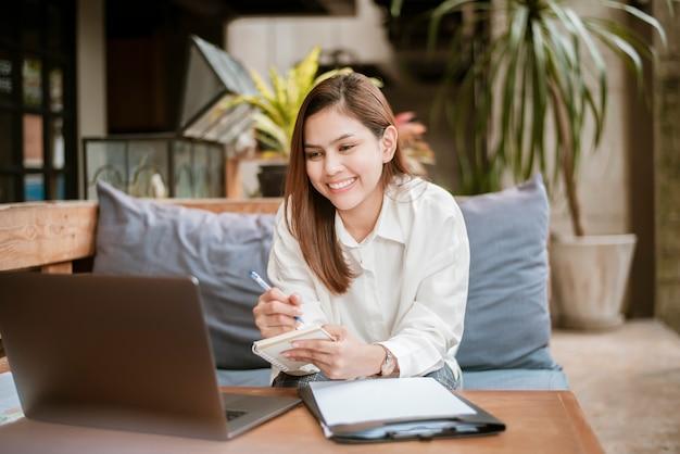 Mulher de negócios linda está trabalhando com o seu computador portátil na loja de café