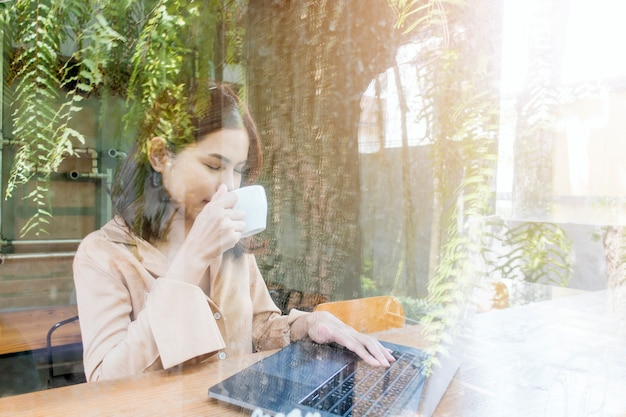 Mulher de negócios linda está trabalhando com seu laptop na cafeteria