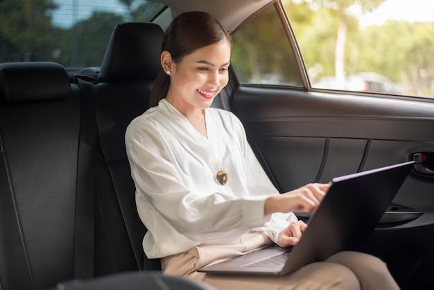 Mulher de negócios linda está trabalhando no carro
