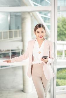Mulher de negócios linda está usando telefone inteligente para os negócios
