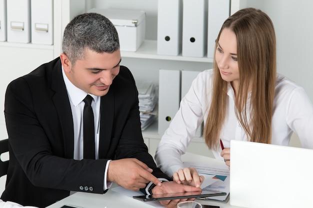 Mulher de negócios linda jovem consultoria com seu colega mostrando algo no tablet pc. parceiros discutindo documentos e ideias