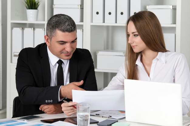 Mulher de negócios linda jovem consultoria com seu colega. parceiros discutindo documentos e ideias
