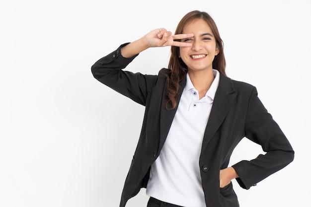 Mulher de negócios linda vestindo terno preto, sorrindo com paz, fazendo gesto com dois dedos na fr ...