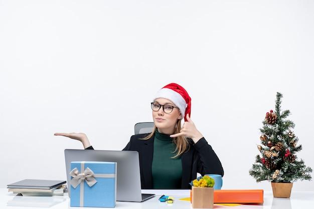 Mulher de negócios loira com chapéu de papai noel sentada a uma mesa com uma árvore de natal e um presente nela fazendo um gesto de me ligar e apontando algo do lado direito no escritório sobre fundo branco