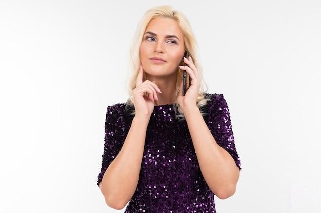 Mulher de negócios loira deslumbrante em vestido roxo brilhante, discutindo negócios ao telefone sobre um fundo branco, com espaço de cópia