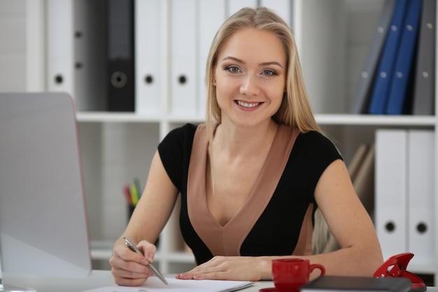 Mulher de negócios loira em treinamento, faz anotações em papel e olha para a câmera.