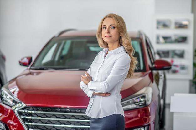 Mulher de negócios loira em uma concessionária de automóveis