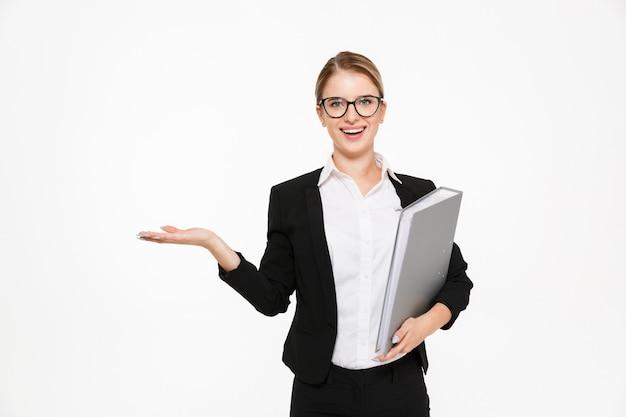 Mulher de negócios loira feliz em óculos com pasta na mão segurando copyspace na libra e parede branca