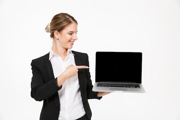 Mulher de negócios loira feliz mostrando a tela do computador laptop em branco enquanto olhando e apontando para ele sobre parede branca