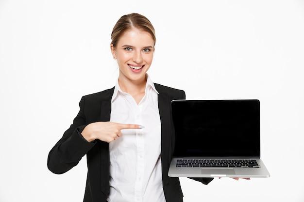 Mulher de negócios loira feliz mostrando a tela do computador portátil em branco e apontando para ele enquanto sobre parede branca