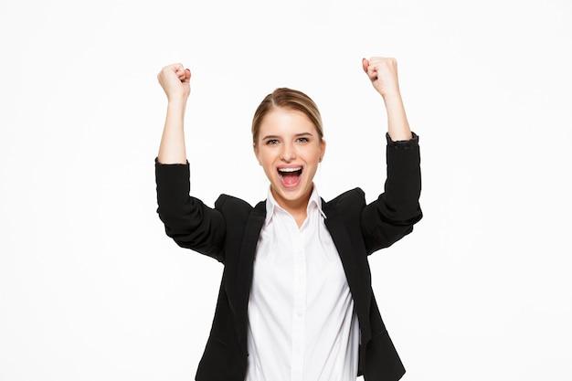 Mulher de negócios loira gritando feliz sobre parede branca