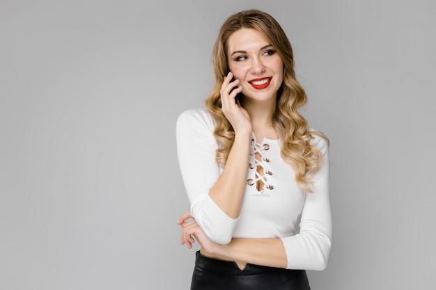 Mulher de negócios loira jovem atraente em roupas preto e branco, sorrindo, falando no telefone em pé no escritório em fundo cinza