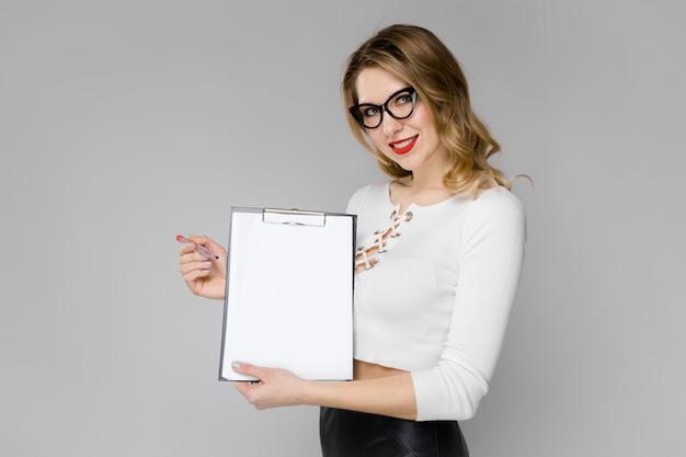 Mulher de negócios loira jovem atraente em roupas preto e branco, sorrindo mostrando a área de transferência nas mãos de pé no escritório em cinza