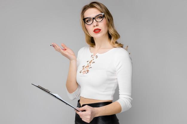 Mulher de negócios loira jovem atraente em roupas preto e branco, sorrindo segurando a área de transferência no escritório em fundo cinza