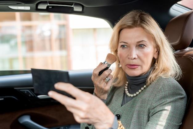 Mulher de negócios loira madura aplicando blush nas bochechas e se olhando no pequeno espelho no banco de trás do táxi enquanto corre para o trabalho