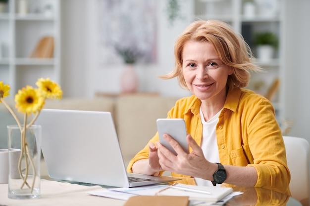Mulher de negócios loira madura sorridente com smartphone olhando para você enquanto trabalhava remotamente na frente do laptop em quarentena