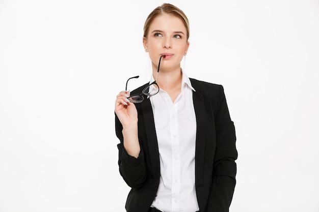 Mulher de negócios loira pensativa manhoso segurando óculos e olhando para cima sobre branco