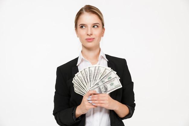 Mulher de negócios loira pensativa sorridente segurando dinheiro e olhando para longe sobre parede branca