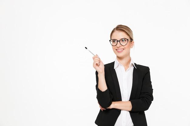 Mulher de negócios loira sorridente em óculos com caneta na mão, tendo a idéia e olhando para longe sobre parede branca