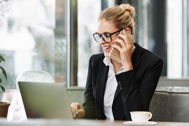 Mulher de negócios loira sorridente, falando por telefone celular