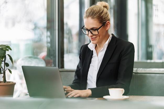 Mulher de negócios loira sorridente usando computador portátil.