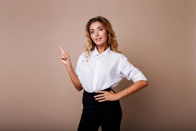 Mulher de negócios loiro apontando para cima e olhando na parede bege. vestindo roupas de trabalho elegantes. copie o espaço para o texto.