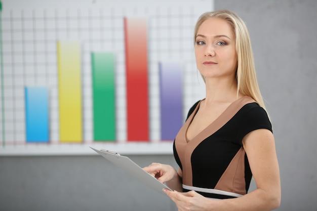 Mulher de negócios loiro segurando uma pasta nas mãos em um fundo de gráficos