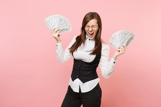 Mulher de negócios louca jovem em copos gritando segurar pacote muitos dólares, dinheiro espalhando as mãos isoladas no fundo rosa. senhora chefe. riqueza de carreira de realização. copie o espaço para anúncio.