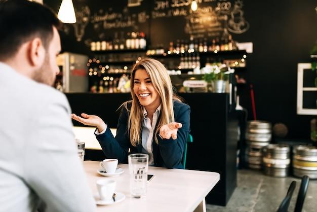 Mulher de negócios loura de sorriso que aprecia em uma primeira data.