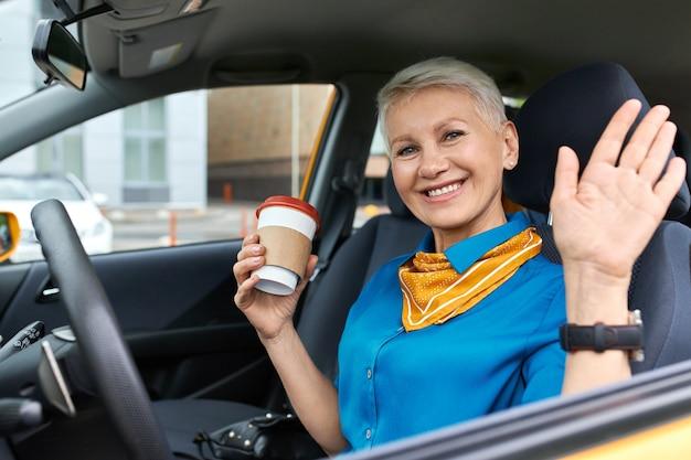 Mulher de negócios madura alegre confiante com cabelo loiro curto, sentada na carteira do motorista, segurando um copo de papel descartável
