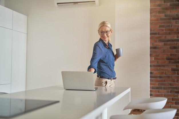 Mulher de negócios madura alegre sorrindo, bebendo café e usando o laptop enquanto está em pé