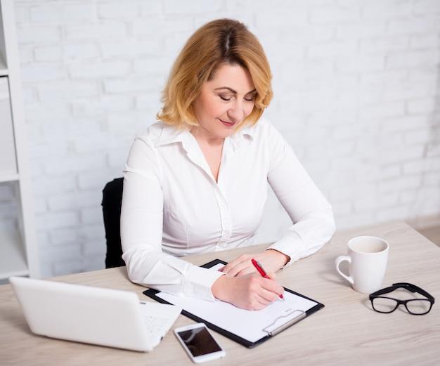 Mulher de negócios madura alegre trabalhando no escritório, escrevendo algo na área de transferência