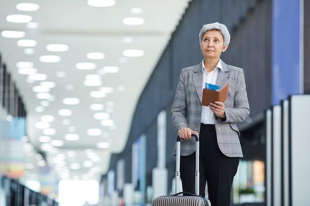 Mulher de negócios madura com bagagem e passagens vai viajar de avião