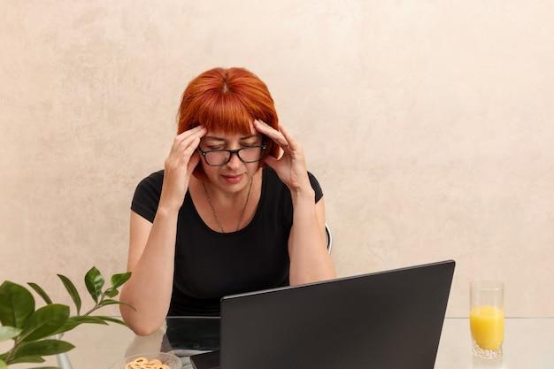 Mulher de negócios madura com dor de cabeça