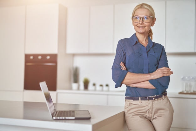 Mulher de negócios madura confiante em copos sorrindo à parte trabalhando em casa usando laptop em pé com