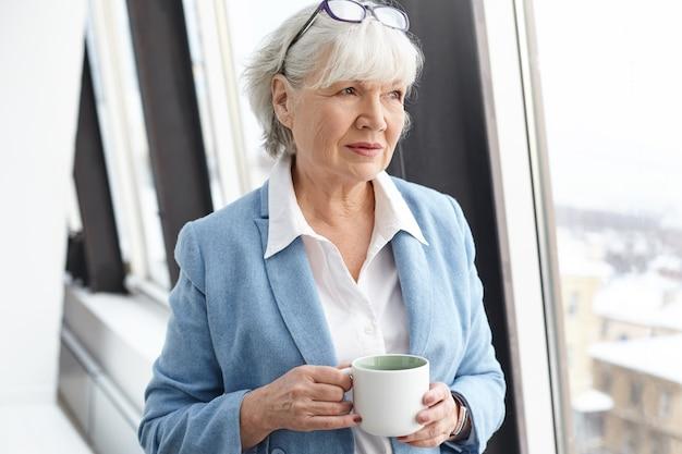 Mulher de negócios madura de cabelos grisalhos séria usando óculos na cabeça e elegantes roupas formais, desfrutando de um café quente, em pé na janela com a xícara nas mãos, com um olhar pensativo e pensativo