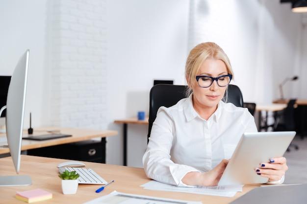 Mulher de negócios madura e atraente trabalhando no escritório com o tablet pc