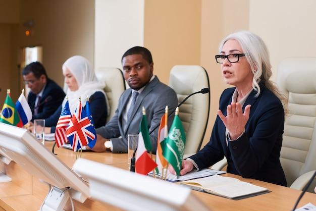 Mulher de negócios madura e bem vestida explicando pontos de seu relatório para o público enquanto está sentada entre outros delegados