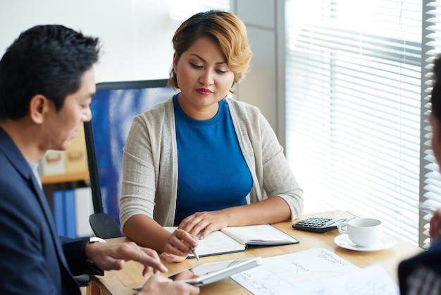 Mulher de negócios madura elegante apontando para um tablet com um apresentador e pedindo a um colega para contar mais sobre sua ideia
