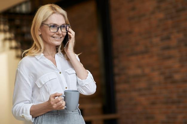 Mulher de negócios madura elegante com cabelo loiro e óculos, segurando uma xícara de café ou chá enquanto