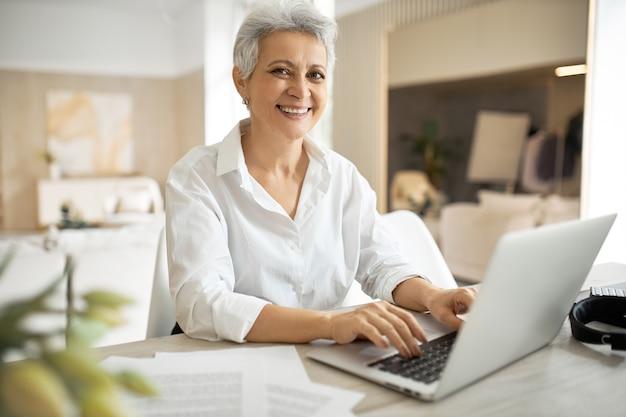 Mulher de negócios madura elegante com corte de cabelo curto sentada em frente ao laptop, olhando para a tela com a boca aberta como se estivesse dizendo algo