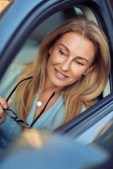 Mulher de negócios madura feliz sentada atrás do volante de seu carro moderno, segurando óculos e